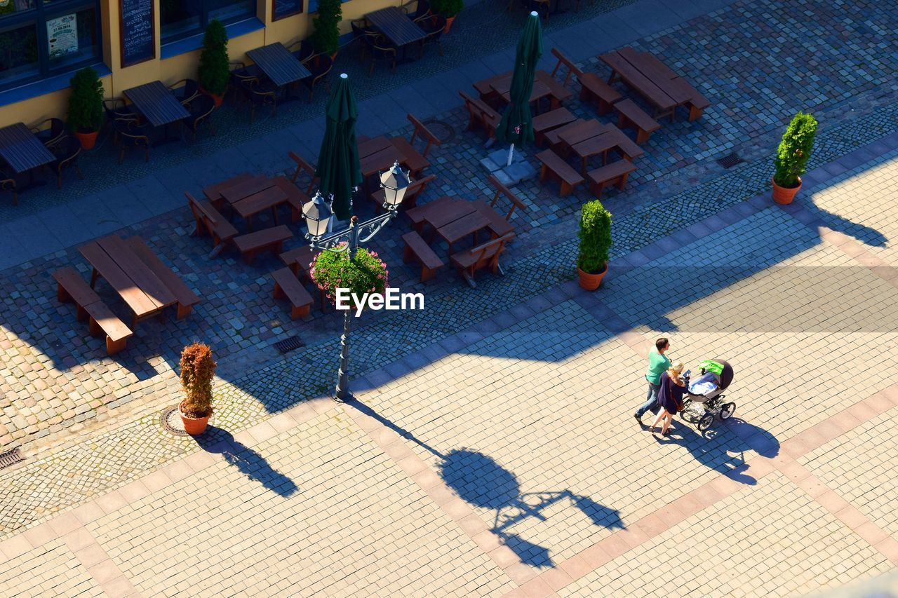 High Angle View Of Man And Woman Walking By Sidewalk Cafe On Sunny Day
