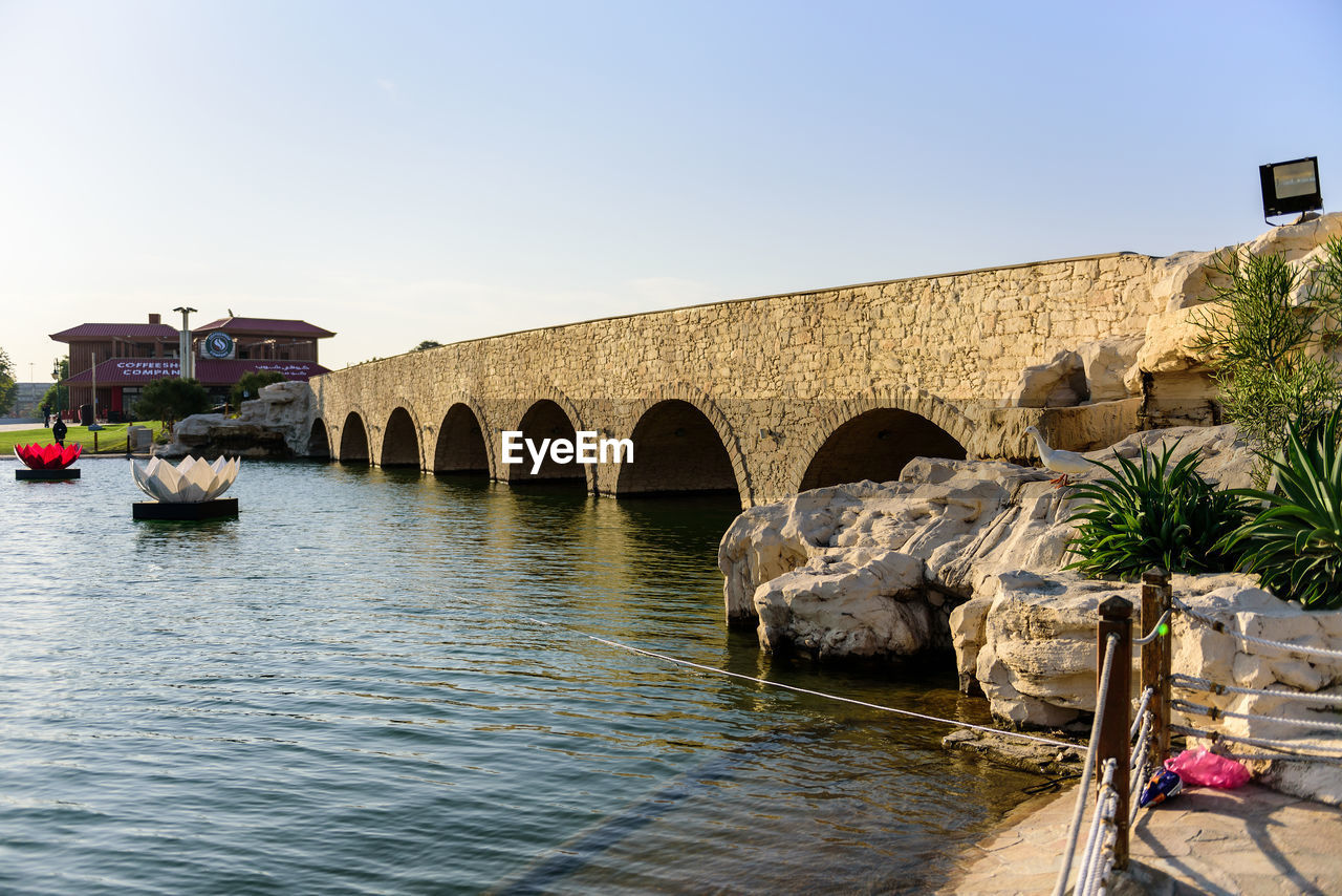 architecture, built structure, water, arch, day, connection, outdoors, building exterior, clear sky, bridge - man made structure, no people, nature, sky