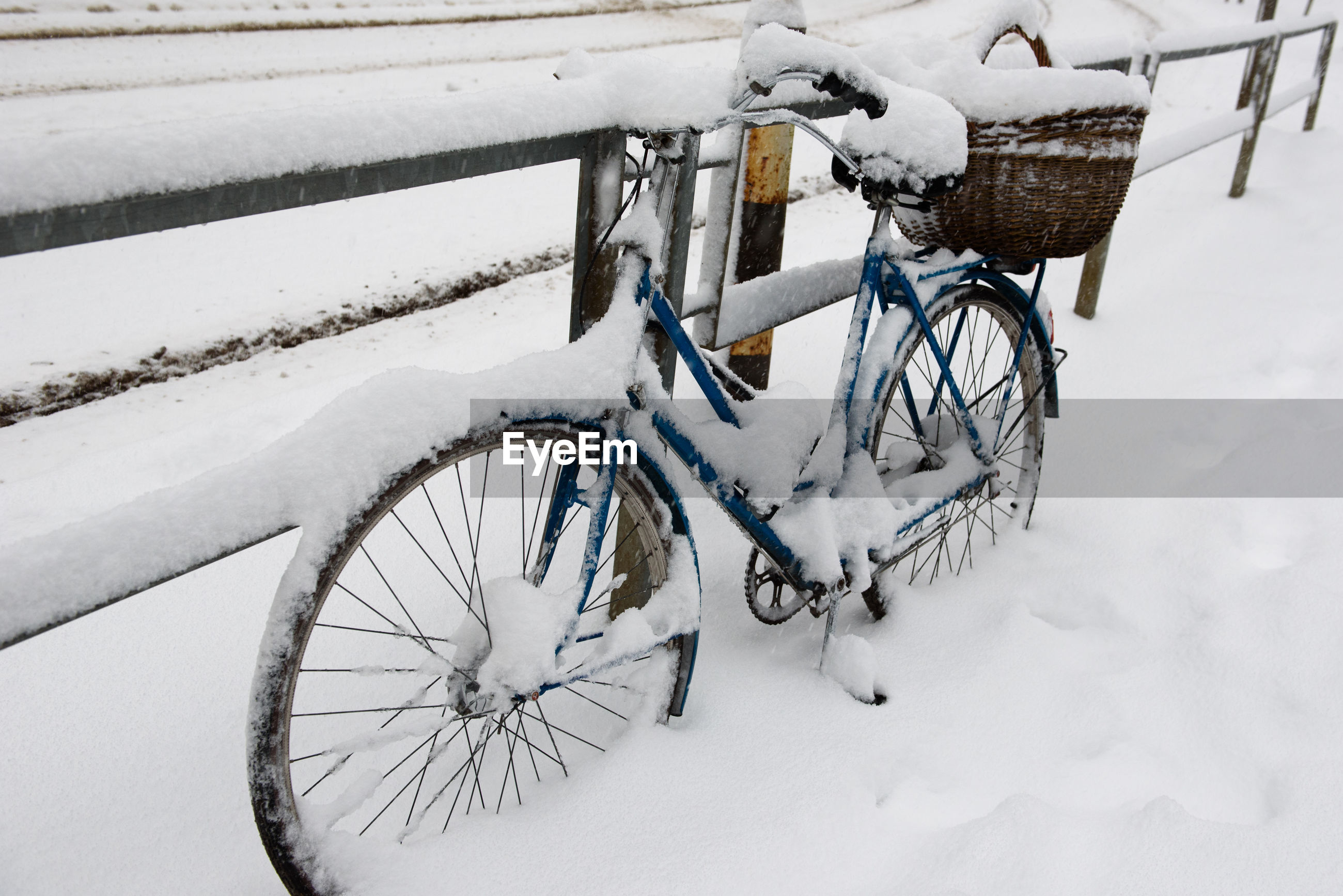 Snow covered bicycle on footpath