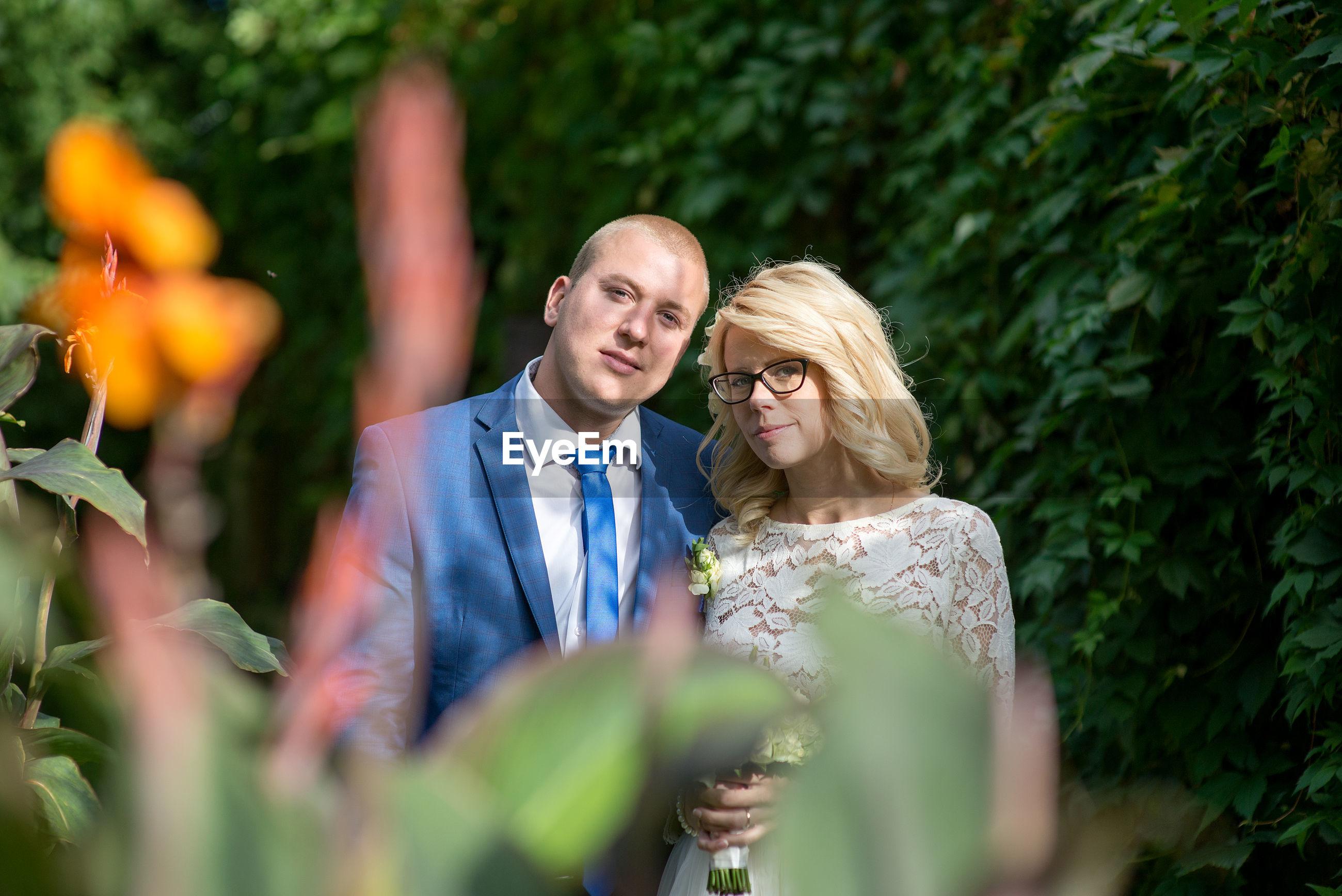 Portrait of bridal couple standing amidst plants at park