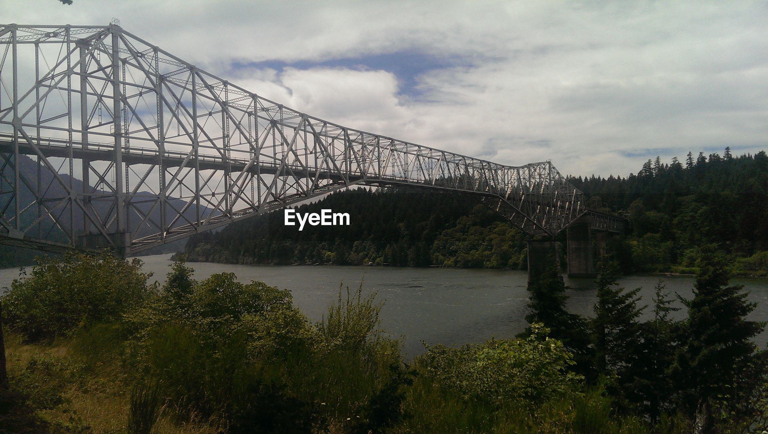Bridge over calm lake against landscape