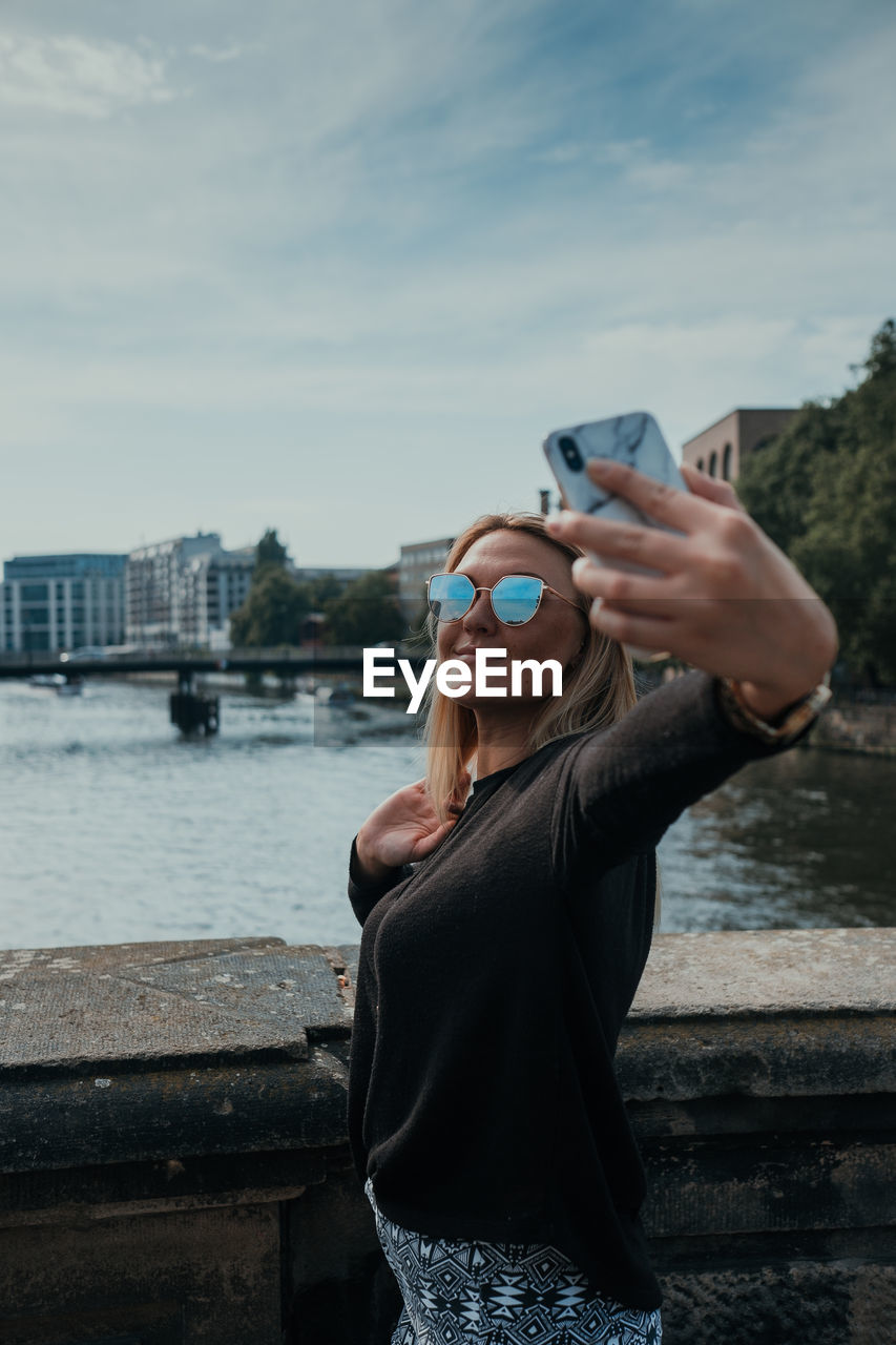 Smiling young woman taking selfie while standing in city