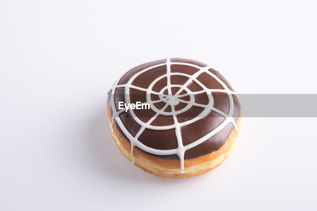 Close-up of donut over white background