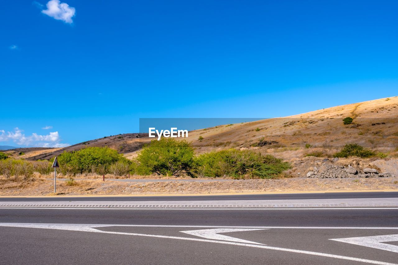 sky, road, blue, transportation, road marking, marking, symbol, no people, day, sign, nature, copy space, beauty in nature, scenics - nature, land, tranquil scene, tranquility, empty road, non-urban scene, sunlight, surface level, arid climate, dividing line