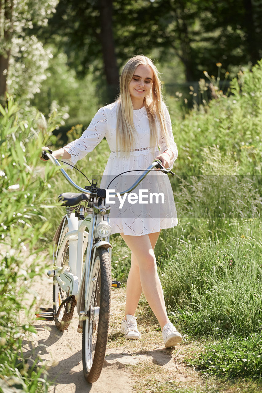 PORTRAIT OF SMILING YOUNG WOMAN BICYCLE