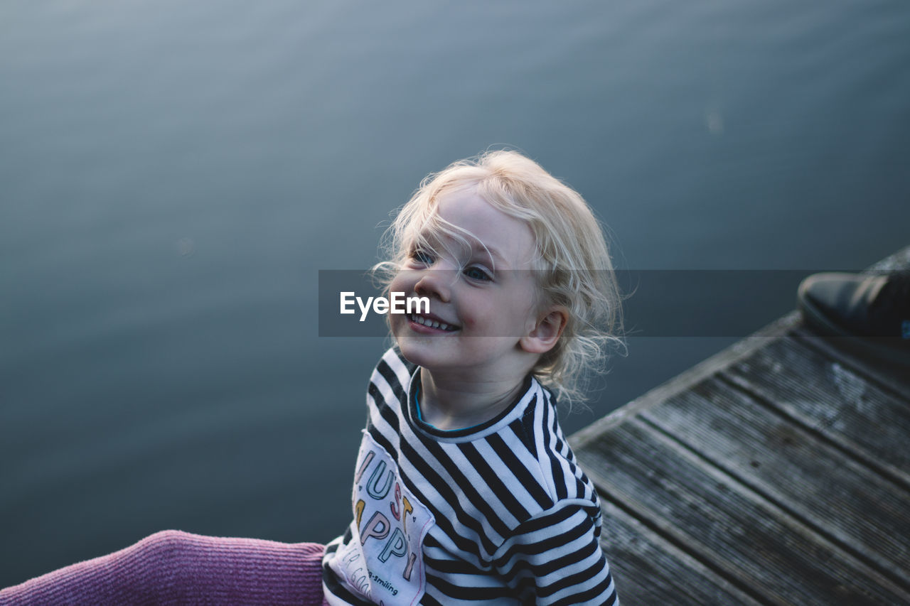 Portrait of smiling girl against water