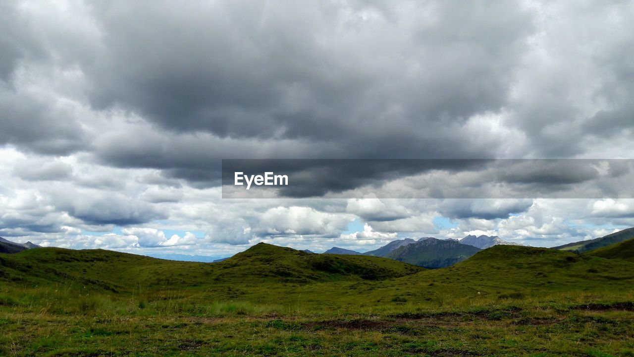 cloud - sky, sky, mountain, scenics - nature, environment, landscape, beauty in nature, nature, day, non-urban scene, tranquil scene, no people, tranquility, storm, land, overcast, green color, storm cloud, plant, outdoors, ominous, above