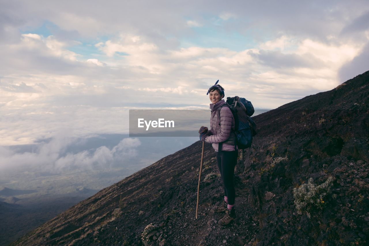 Portrait of smiling hiker standing on mountain against cloudy sky