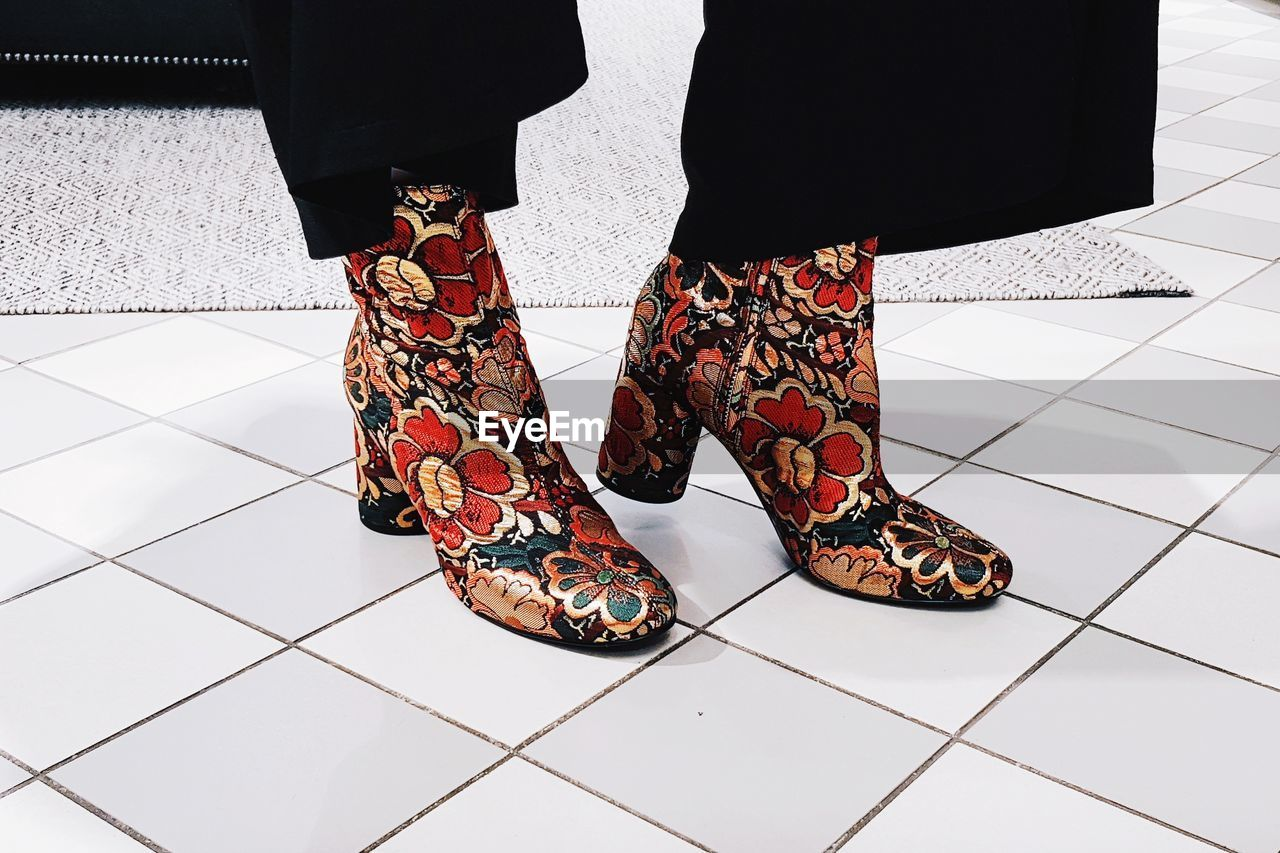 Low section of woman wearing floral patterned shoes while standing on tiled floor