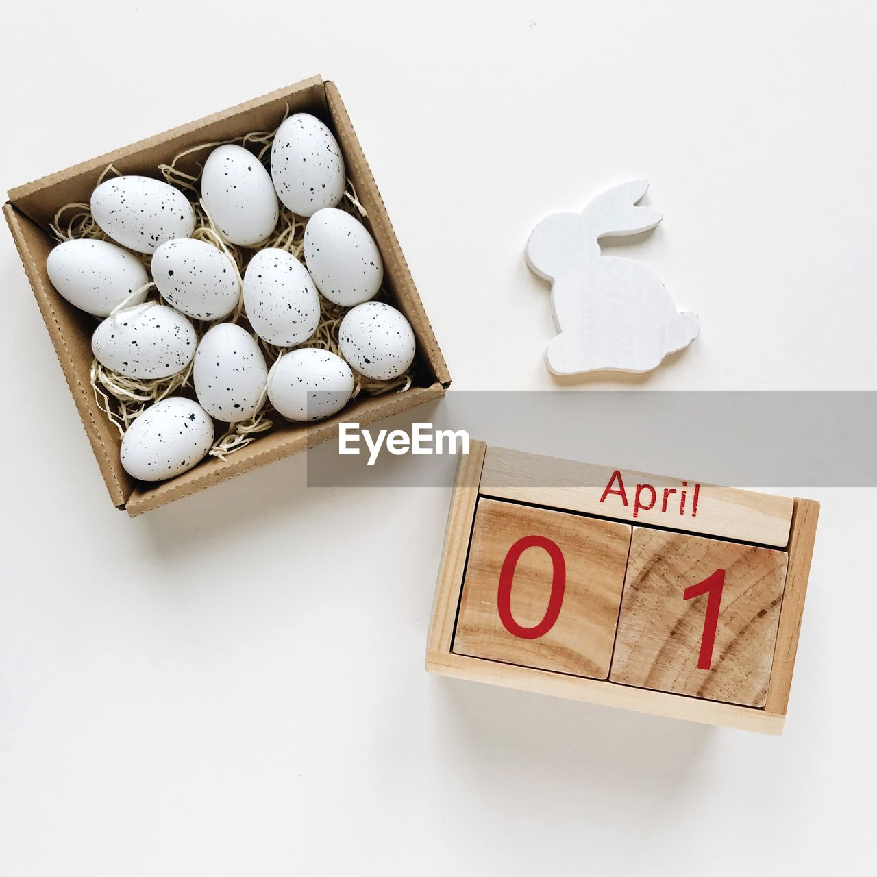 High angle view of eggs and calendar on white background
