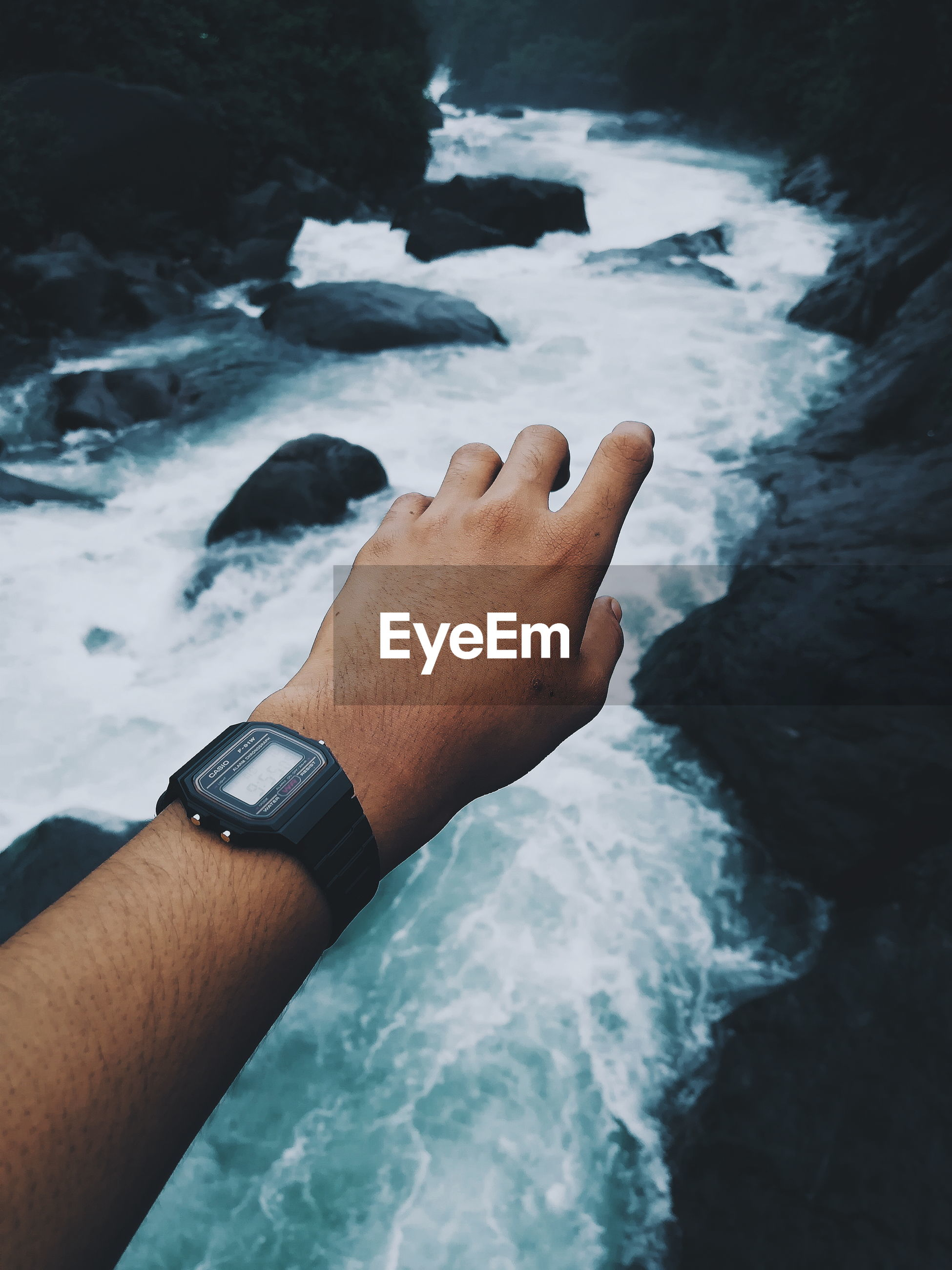 Cropped hand of man wearing wristwatch over stream