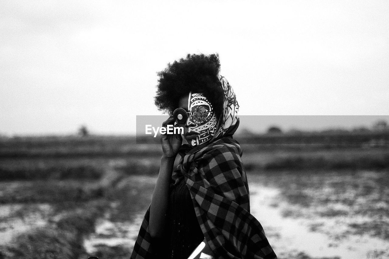 Portrait Of Woman With Face Paint Standing On Field