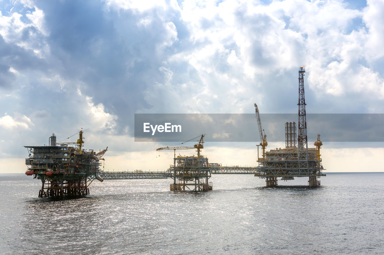 oil industry, water, offshore platform, drilling rig, sky, fuel and power generation, industry, sea, cloud - sky, nature, fossil fuel, built structure, waterfront, machinery, architecture, oil, crude oil, day, crane - construction machinery, no people, outdoors
