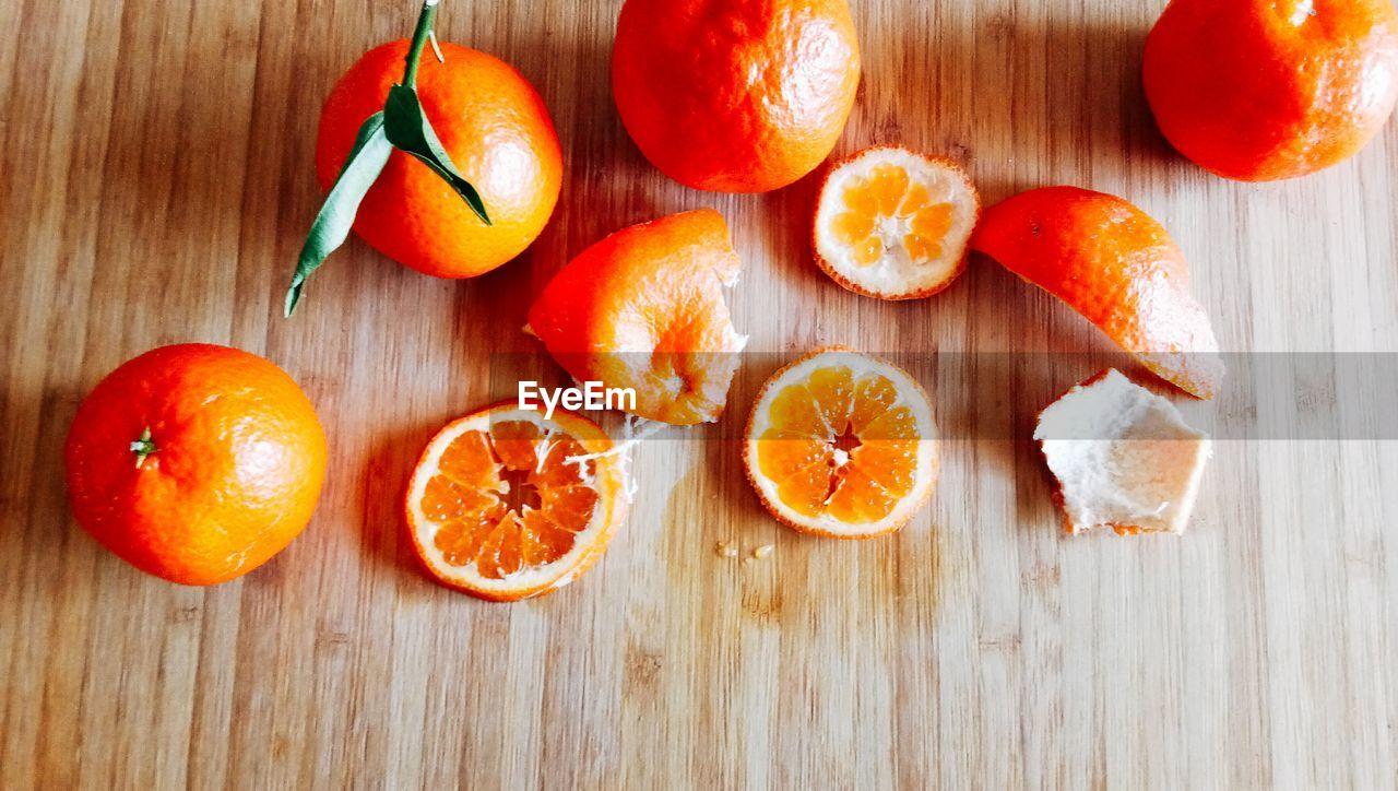 orange - fruit, fruit, orange color, healthy eating, citrus fruit, cross section, freshness, slice, food, food and drink, indoors, wood - material, no people, table, close-up, blood orange, day