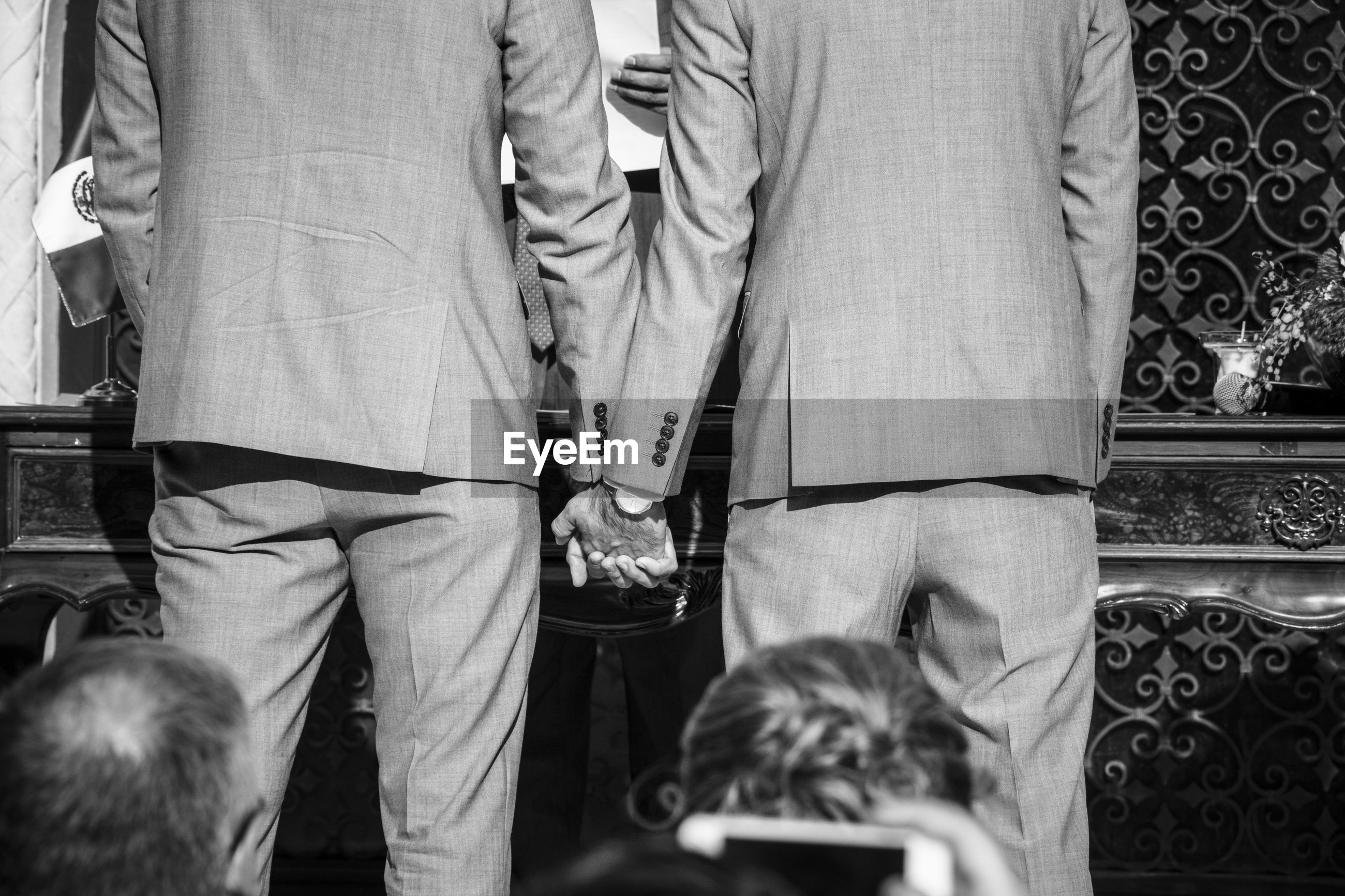 Rear view of gay couple holding hands during wedding ceremony in church
