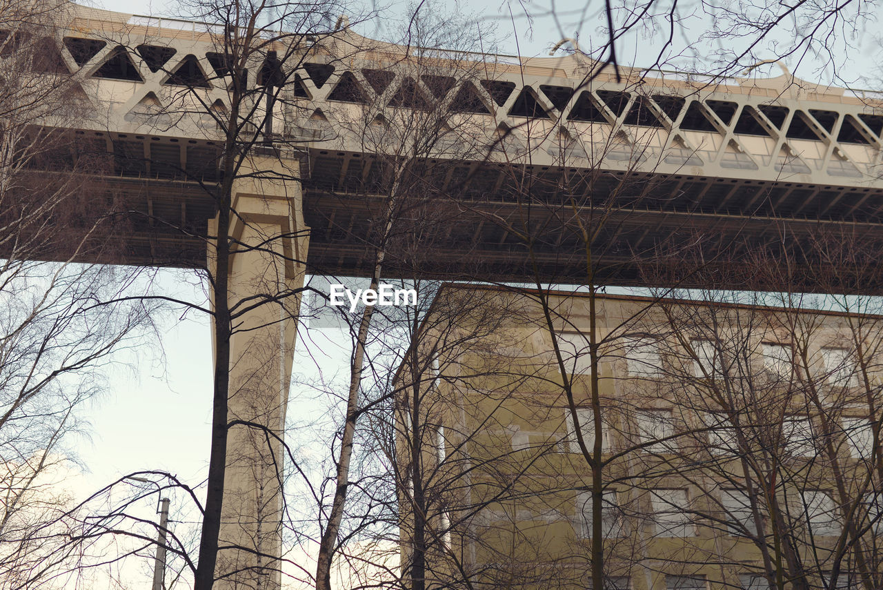 LOW ANGLE VIEW OF BRIDGE AND BARE TREES AGAINST BUILDINGS