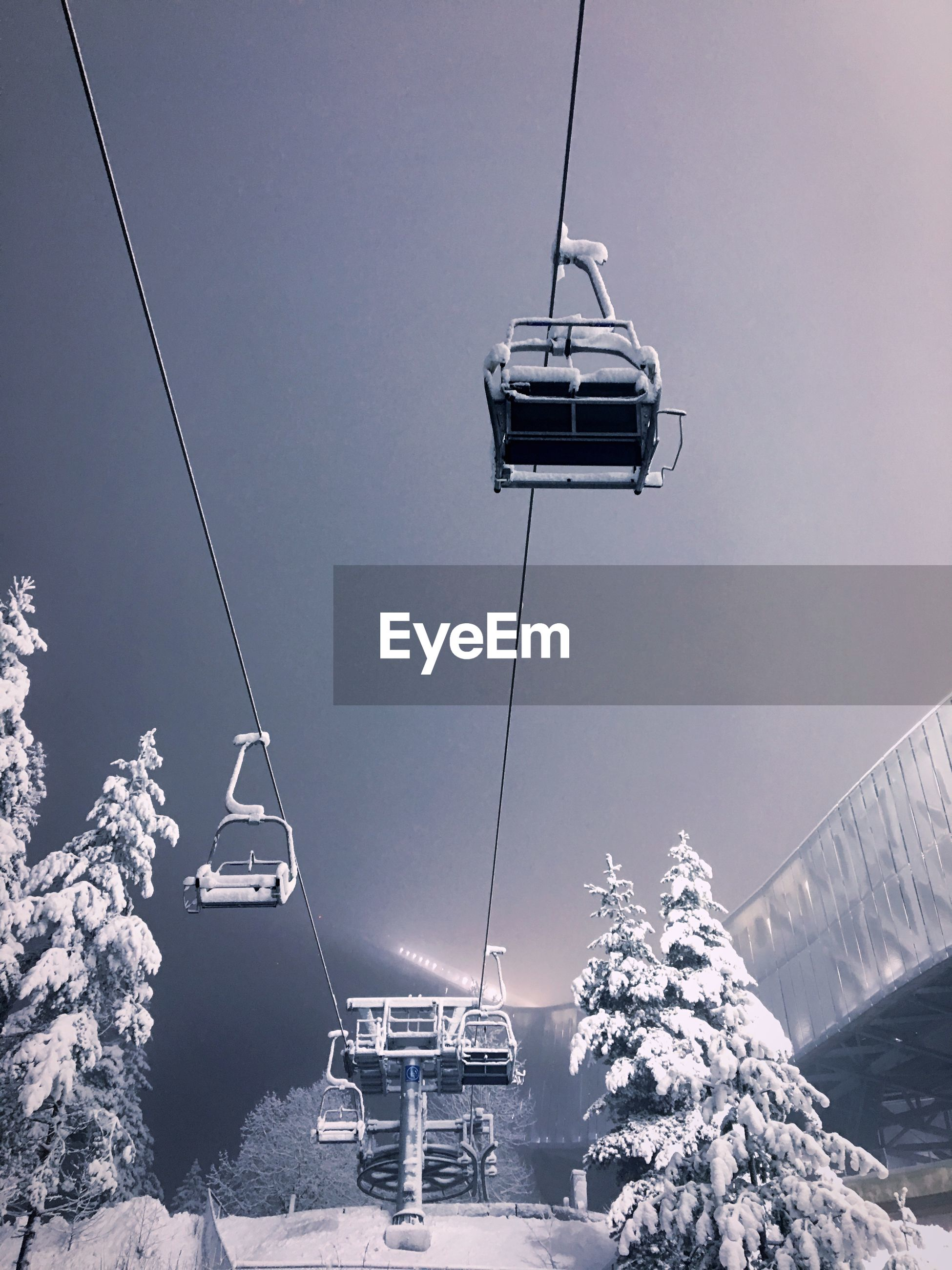 Low angle view of ski lift against sky during winter at night