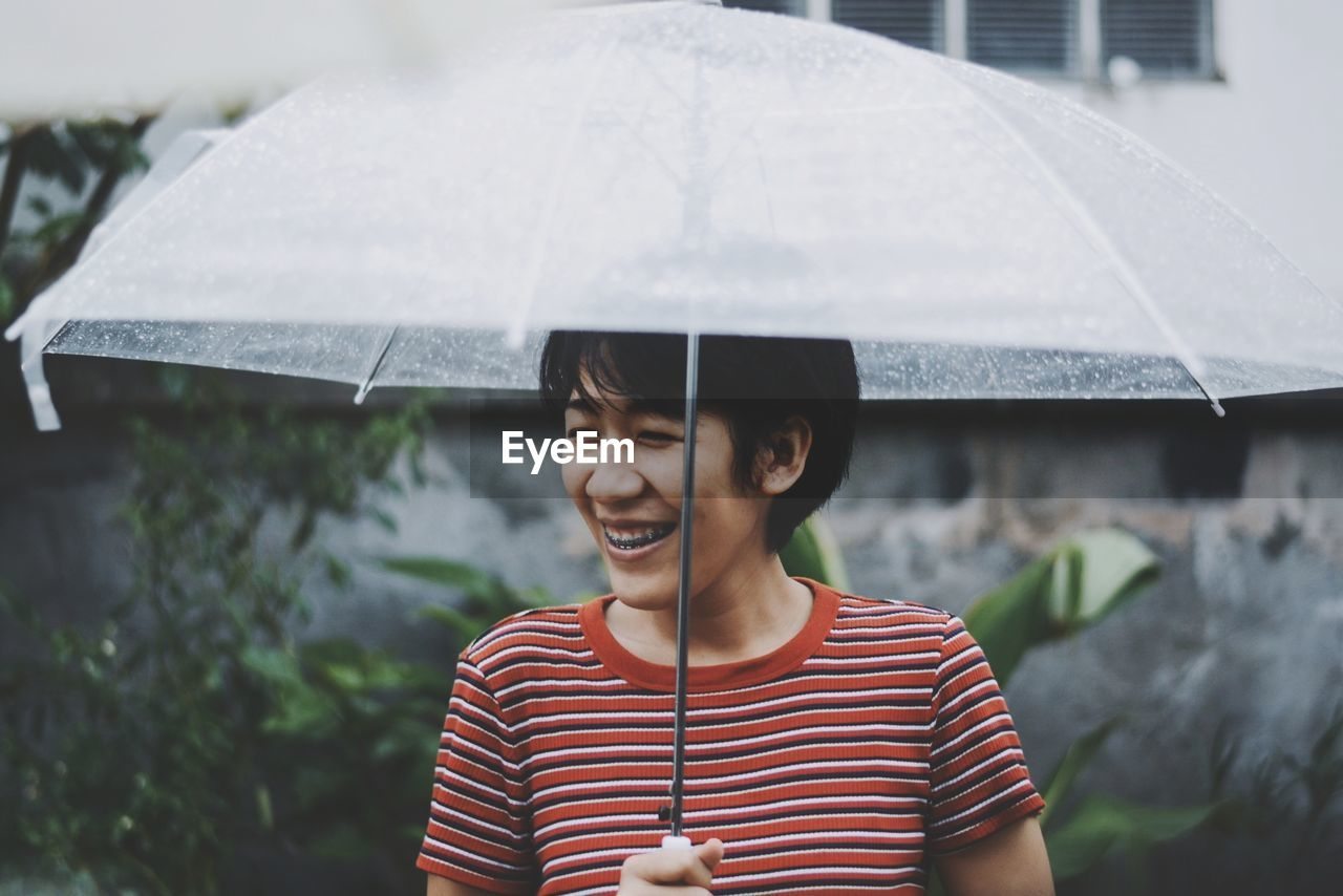 Portrait Of Happy Young Woman In Rain