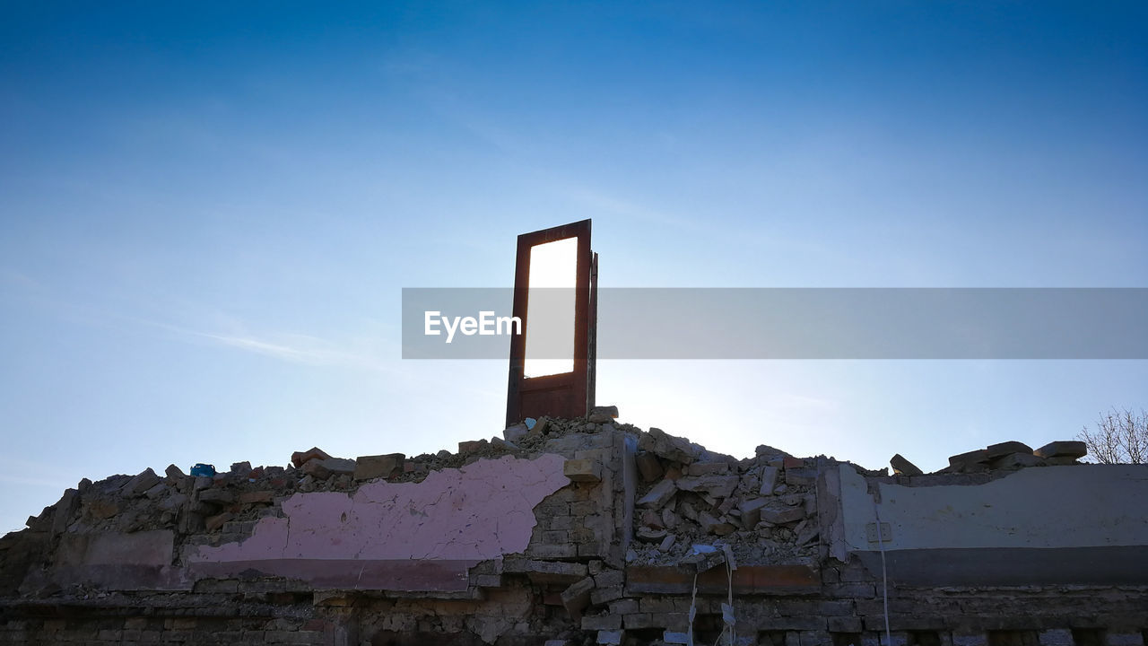 sky, architecture, built structure, building exterior, low angle view, nature, no people, clear sky, copy space, day, building, sunlight, outdoors, blue, house, wall - building feature, abandoned, old, wall, mountain, ruined