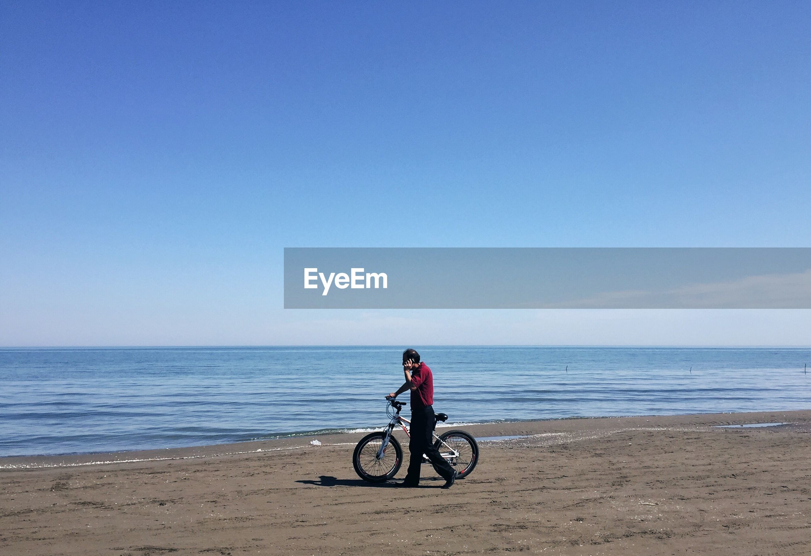 MAN RIDING BICYCLE ON BEACH