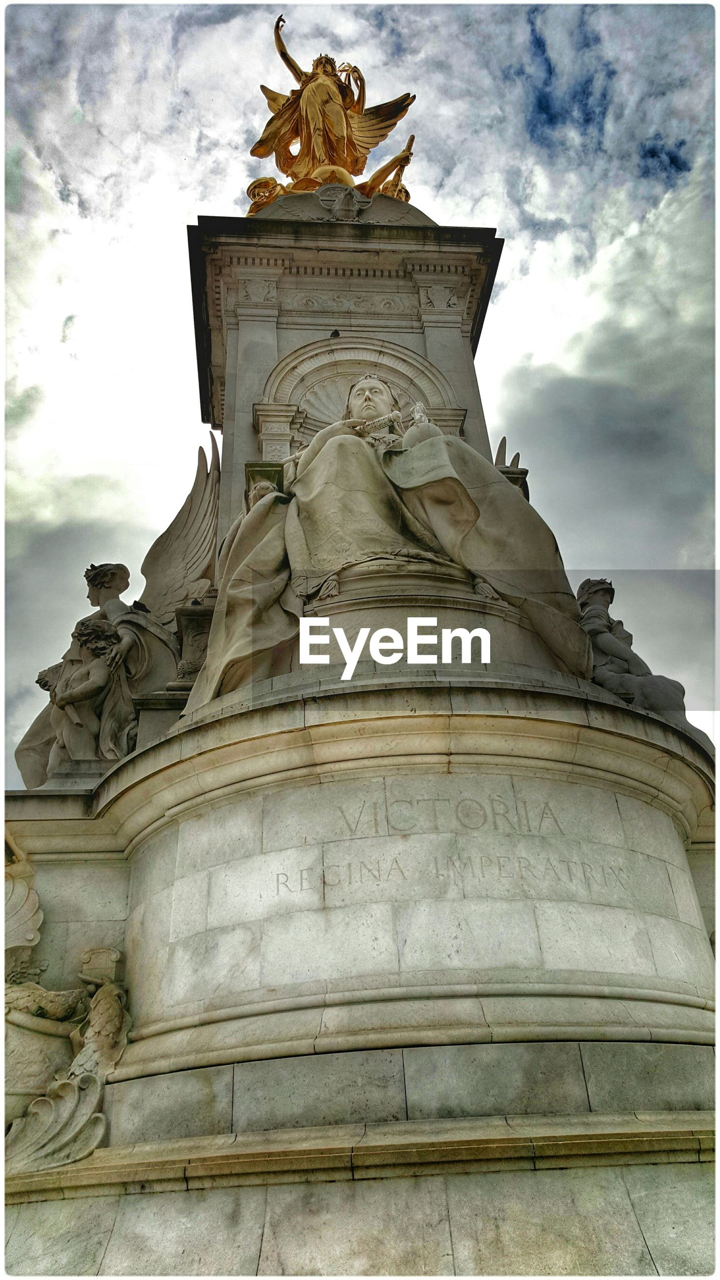 Low angle view of queen victoria's monument against cloudy sky