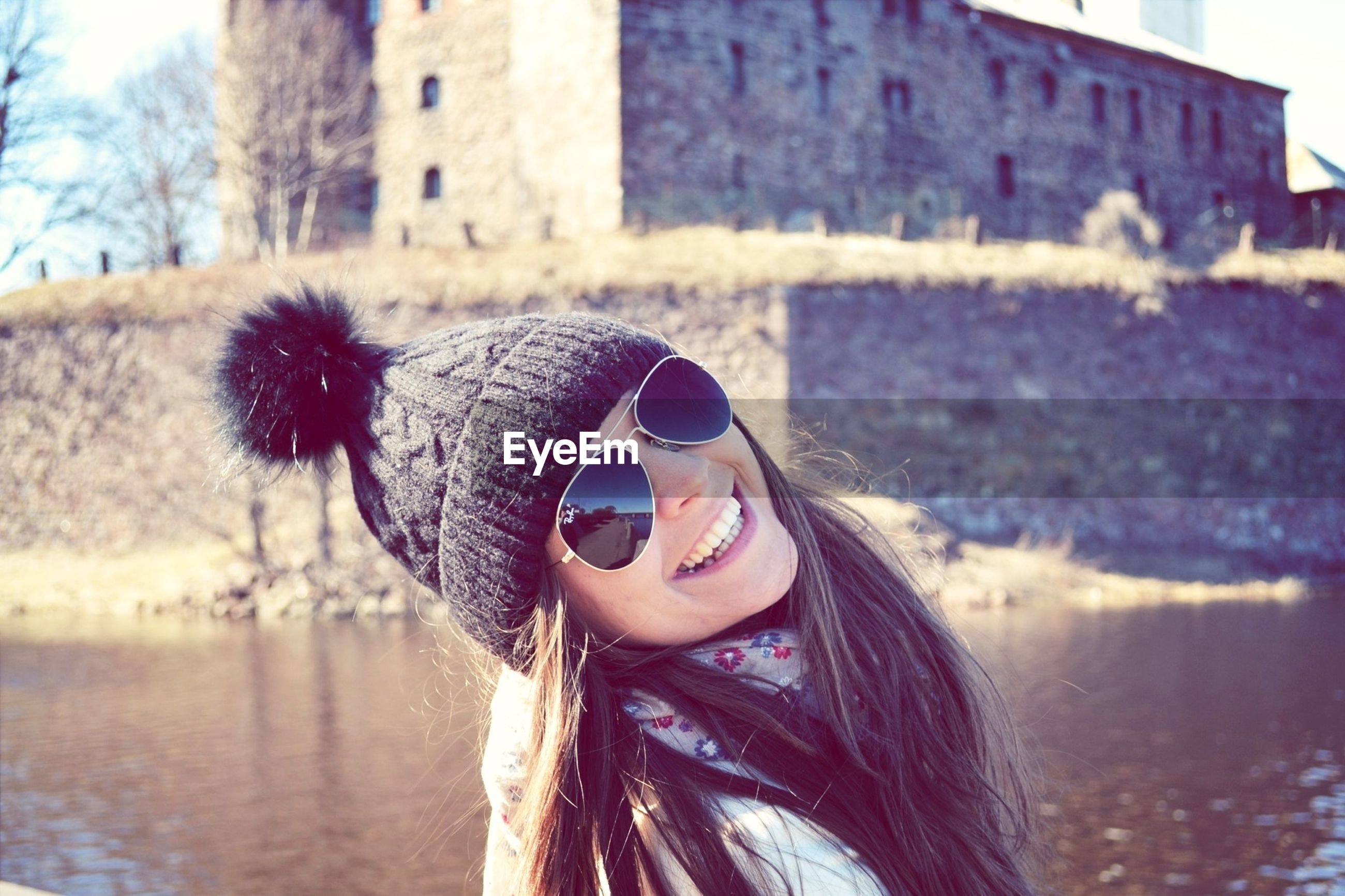 young adult, water, focus on foreground, sunglasses, young women, long hair, lifestyles, leisure activity, portrait, headshot, looking at camera, person, front view, building exterior, day, smiling, built structure