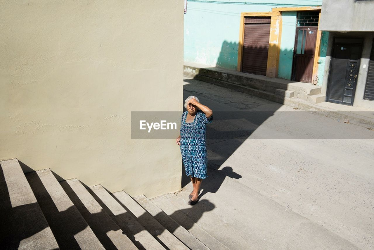 full length, one person, leisure activity, rear view, day, outdoors, sunlight, young adult, built structure, women, real people, architecture, shadow, young women, lifestyles, building exterior, adult, people, adults only