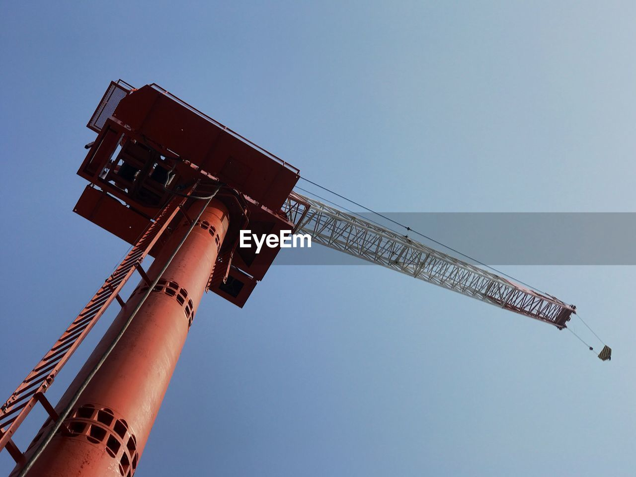 sky, low angle view, clear sky, machinery, industry, nature, day, crane - construction machinery, construction industry, metal, blue, architecture, outdoors, copy space, built structure, construction equipment, no people, tall - high, sunlight, red, place