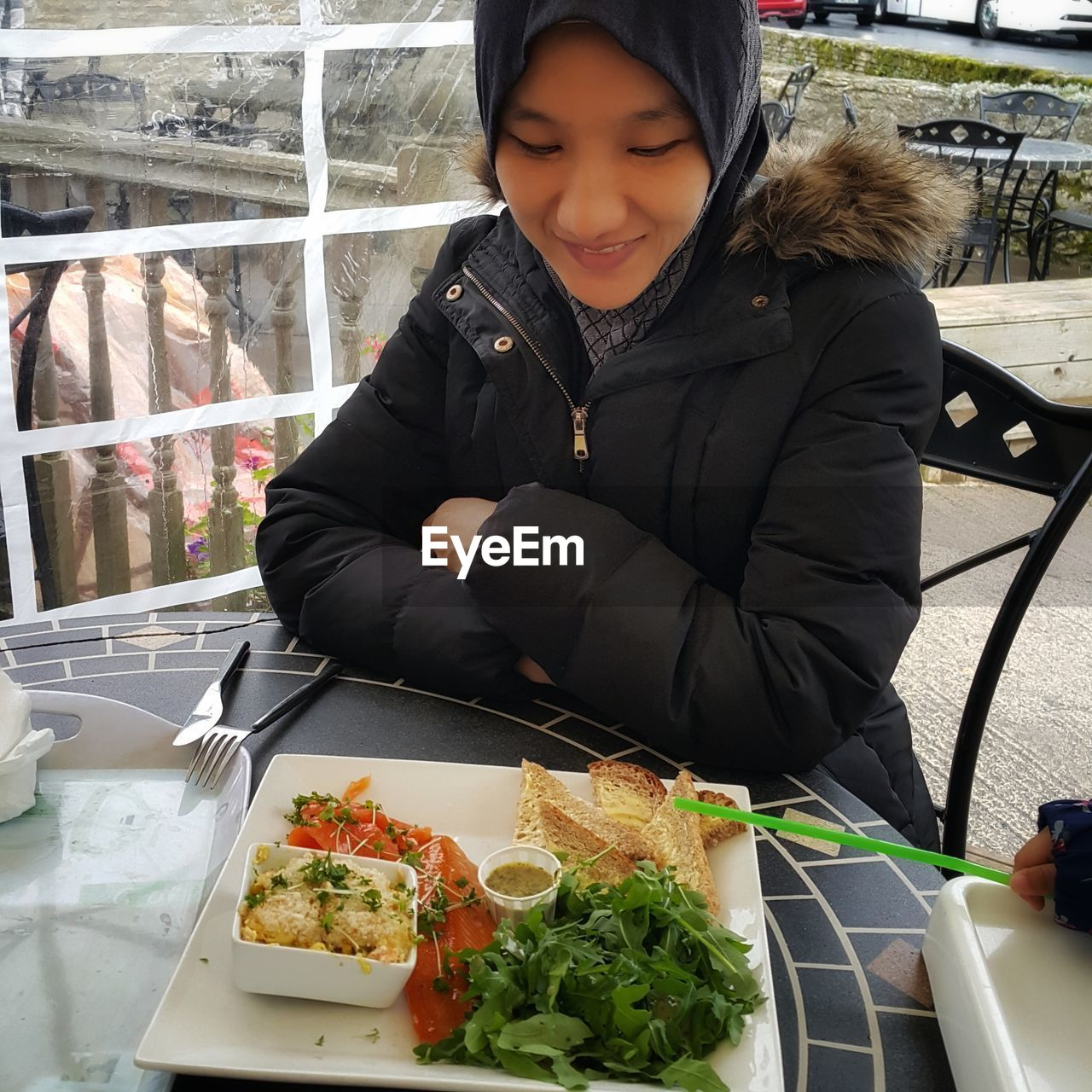 Woman Having Food While Sitting At Outdoor Cafe