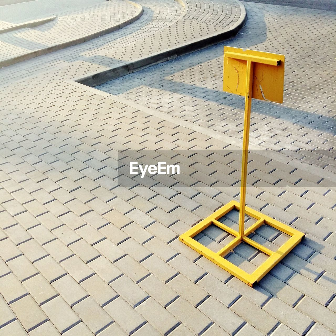 yellow, day, high angle view, no people, outdoors, protection, footpath, security, architecture, playground, pattern, built structure, street, nature, sunlight, metal, seat, absence, safety, design, paving stone