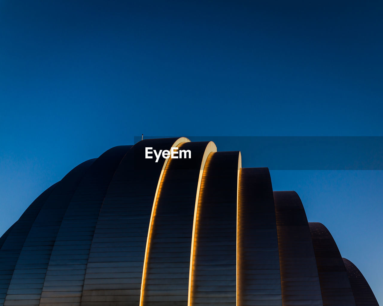 Low Angle View Of Illuminated Modern Building Against Blue Sky