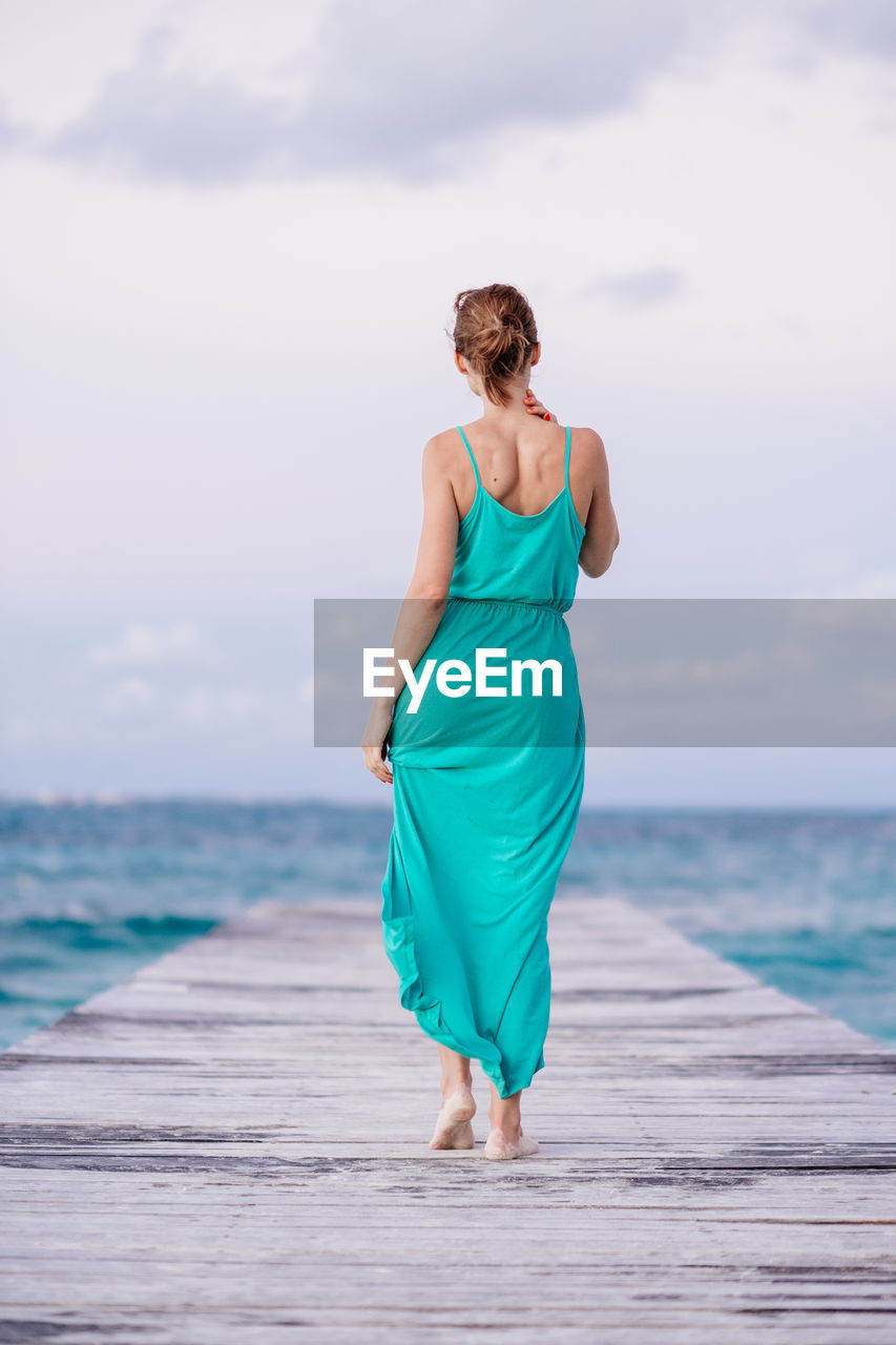 Rear View Of Woman Walking On Pier Against Sea
