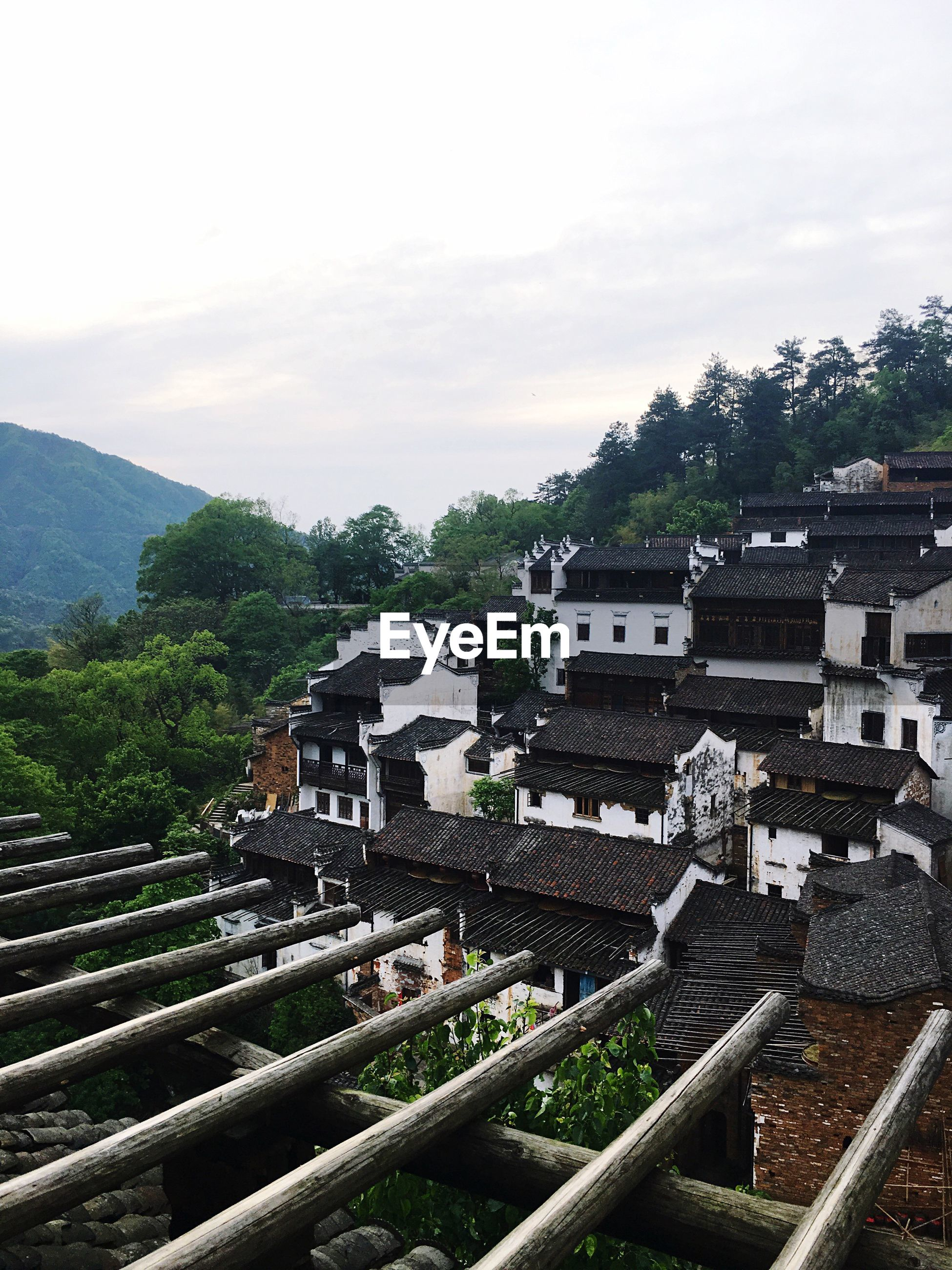 building exterior, architecture, built structure, high angle view, tree, sky, house, roof, residential structure, residential building, mountain, cloud - sky, residential district, railroad track, town, day, city, townscape, cityscape, outdoors