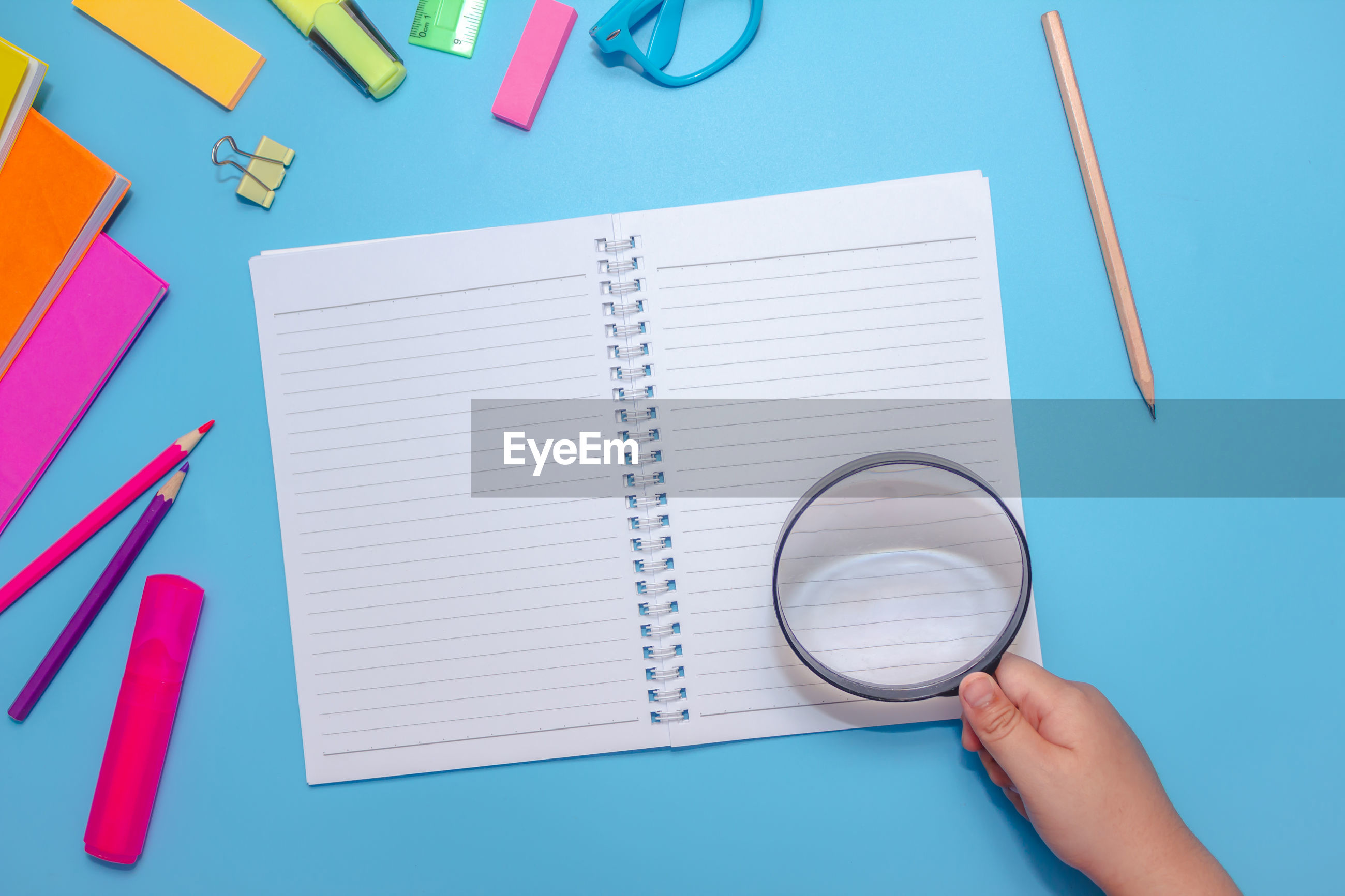 Directly above shot of hand holding magnifying glass over book by objects on blue background