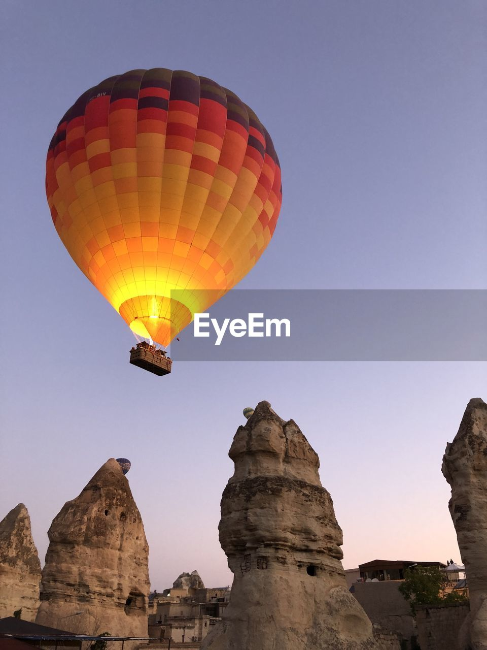 sky, hot air balloon, adventure, rock, rock - object, low angle view, balloon, nature, air vehicle, clear sky, mid-air, flying, rock formation, transportation, travel, solid, sport, parachute, leisure activity, extreme sports, outdoors, formation