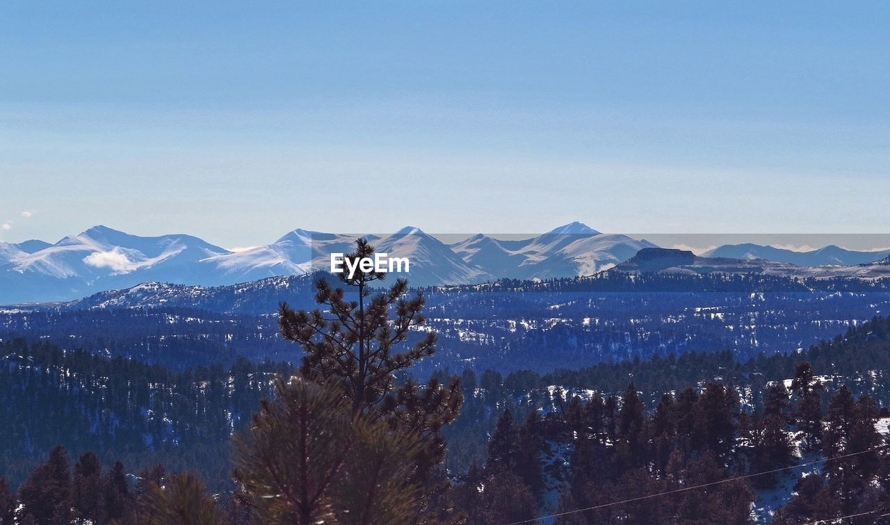 mountain, snow, cold temperature, winter, mountain range, nature, beauty in nature, scenics, tranquility, tranquil scene, snowcapped mountain, landscape, tree, no people, outdoors, day, forest, clear sky, blue, sky