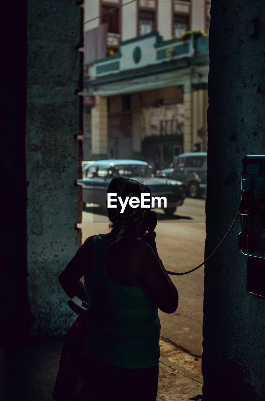 Woman Talking On Payphone In City