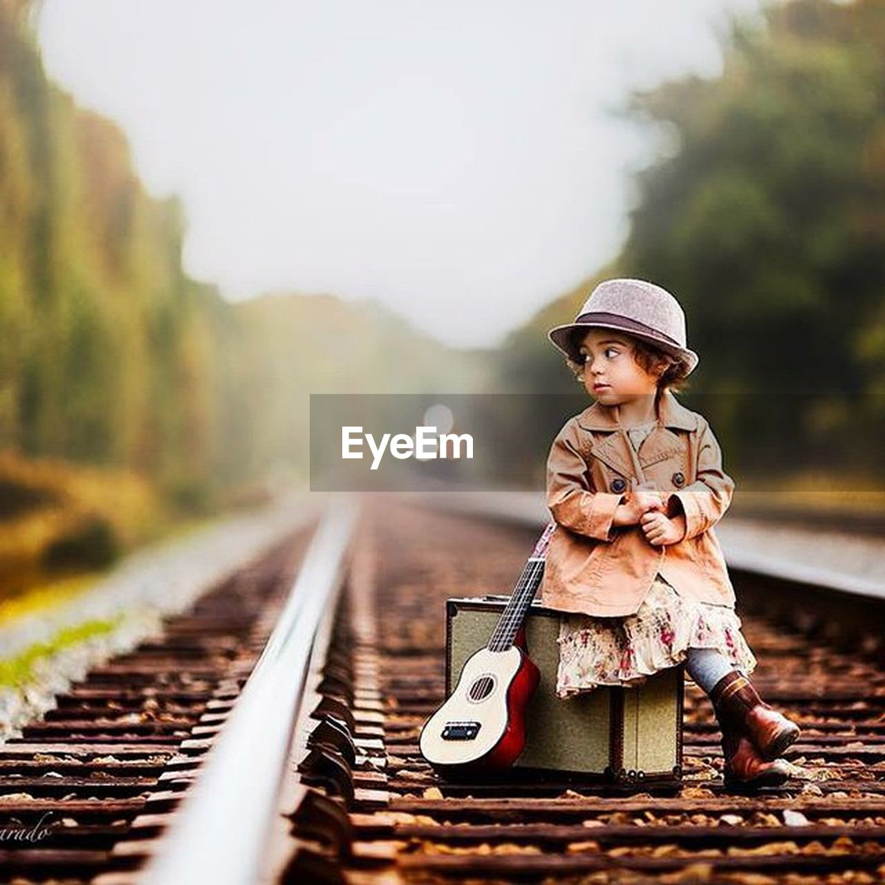 railroad track, hat, child, rail transportation, one person, children only, boys, journey, outdoors, childhood, train - vehicle, people, adventure, transportation, old-fashioned, day, portrait, headwear, adult, one boy only, sky, camouflage clothing