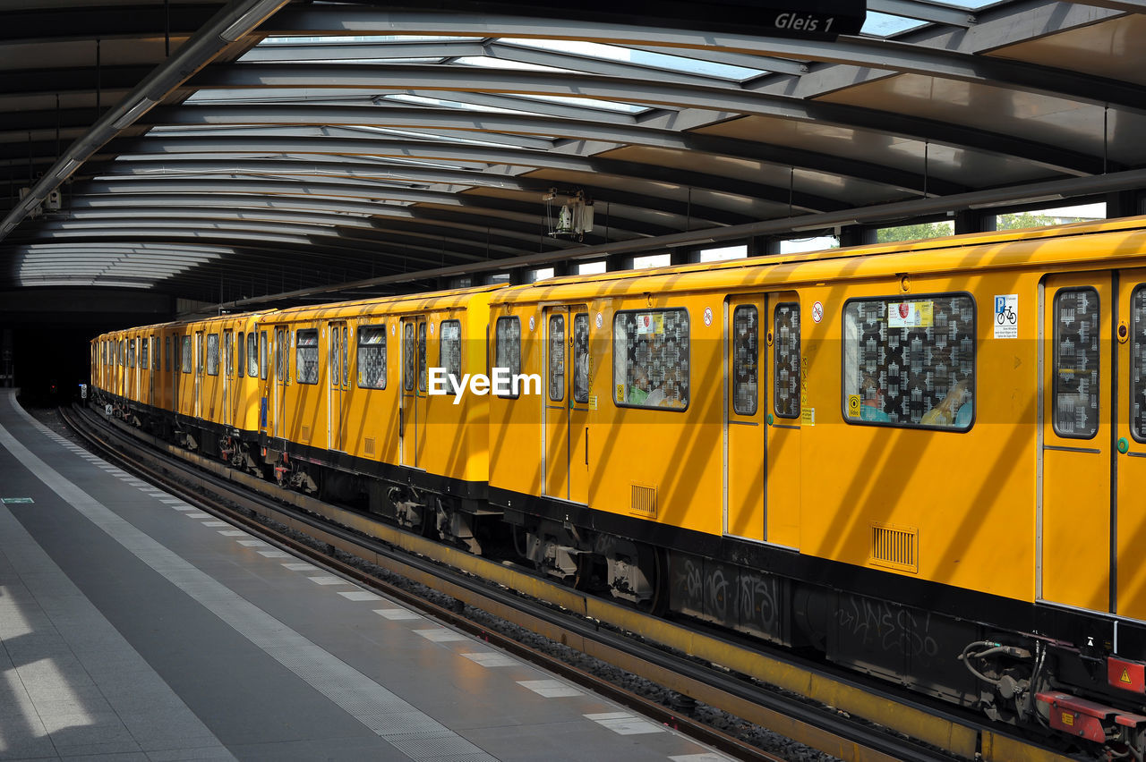rail transportation, mode of transportation, public transportation, transportation, railroad station platform, track, railroad track, train, train - vehicle, railroad station, yellow, architecture, no people, land vehicle, travel, indoors, passenger train, day, subway train, ceiling, station, arrival, railroad car