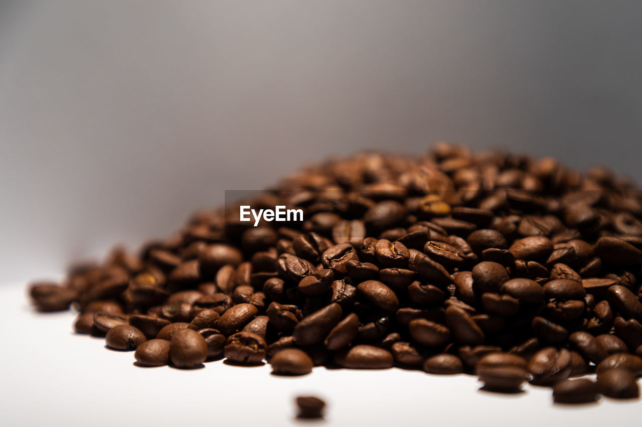 food and drink, roasted coffee bean, brown, coffee - drink, coffee, food, close-up, indoors, still life, freshness, large group of objects, selective focus, no people, studio shot, roasted, table, coffee bean, raw food, copy space, white background, caffeine, temptation