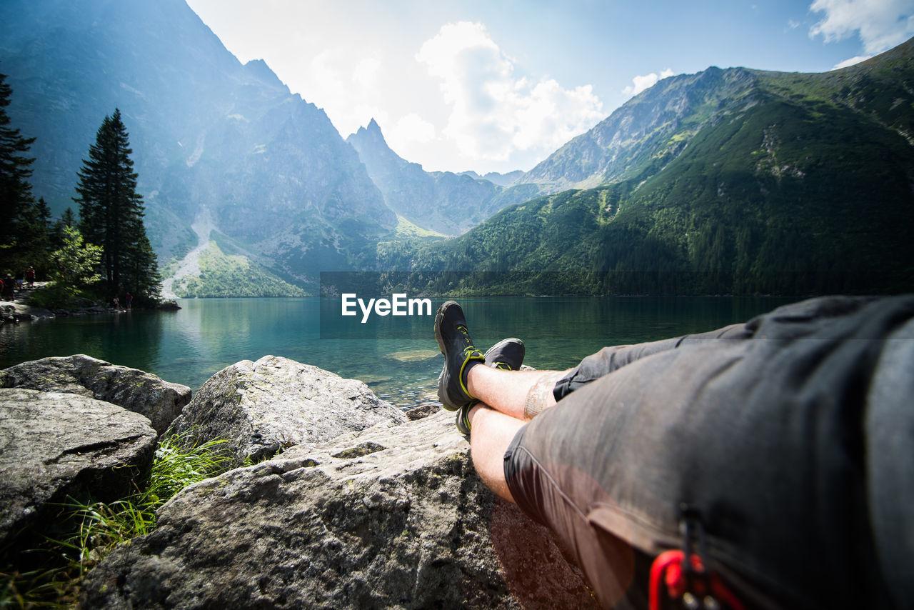 People looking at lake against mountain range