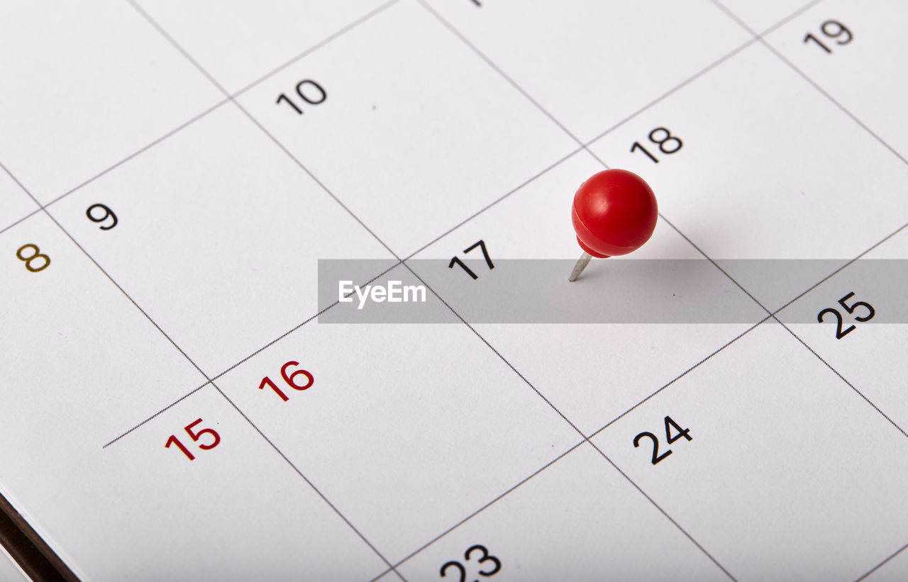 High angle view of thumbtack on calendar