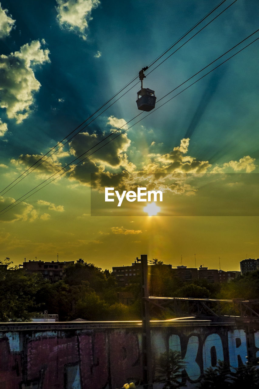sky, cloud - sky, sunset, built structure, architecture, nature, connection, water, building exterior, sunlight, sun, cable, bridge, beauty in nature, bridge - man made structure, cable car, transportation, outdoors, no people