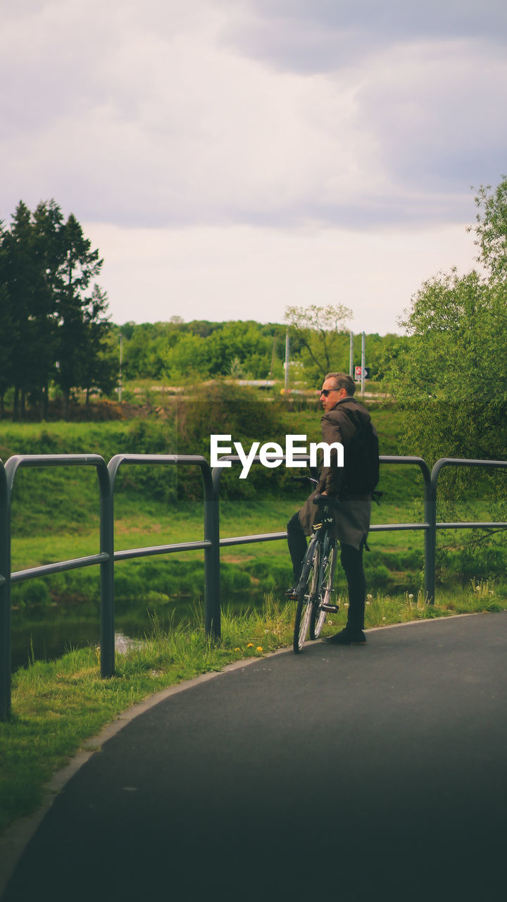 Full length of man with bicycle standing on road by railing