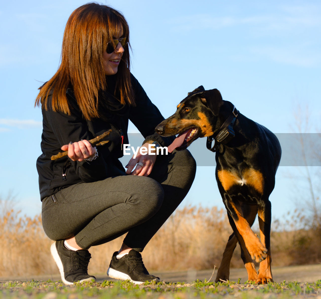 YOUNG WOMAN WITH DOG SITTING ON FIELD