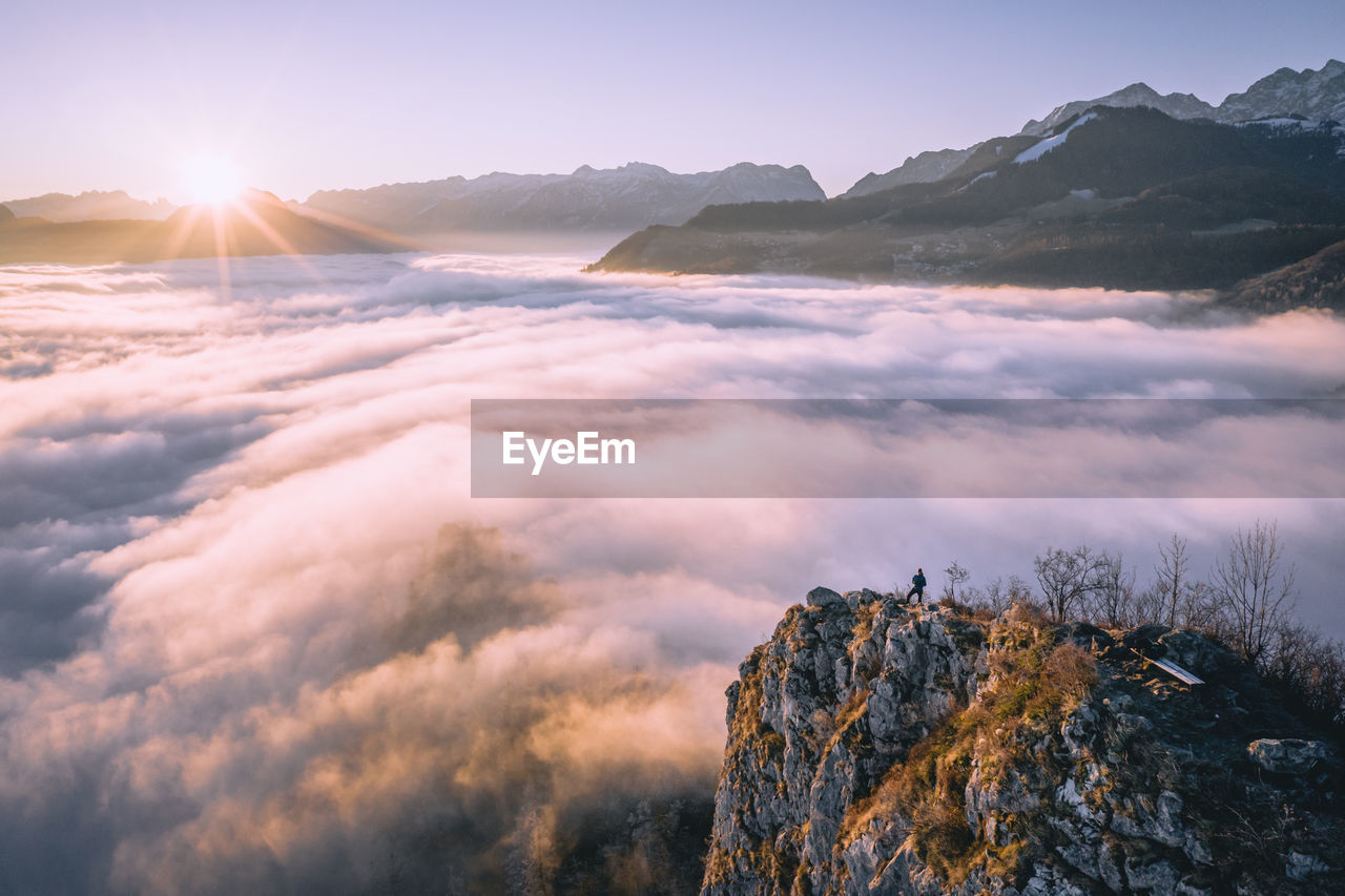 High angle view of man standing on mountain ridge rising above the clouds, hallein, austria