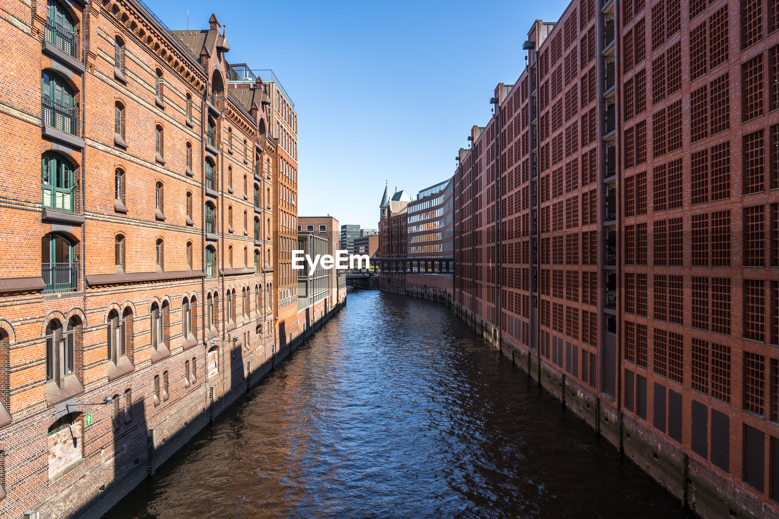Canal amidst buildings against clear sky in city
