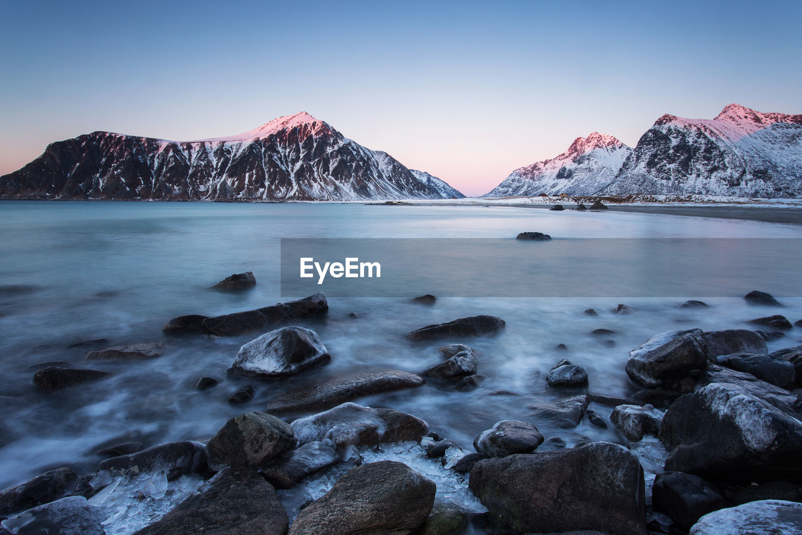Scenic view of sea by snowcapped mountains against sky during winter