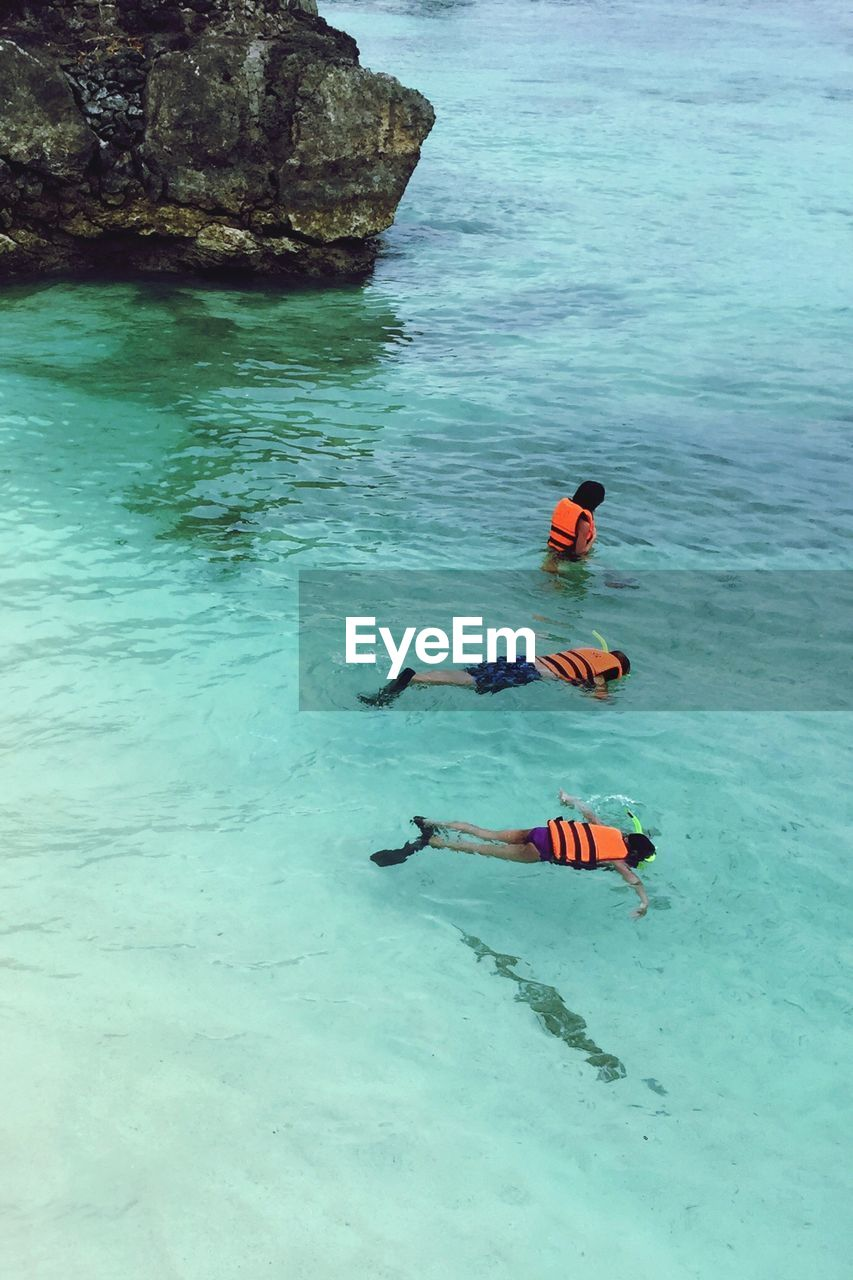 High angle view of friends snorkeling in sea