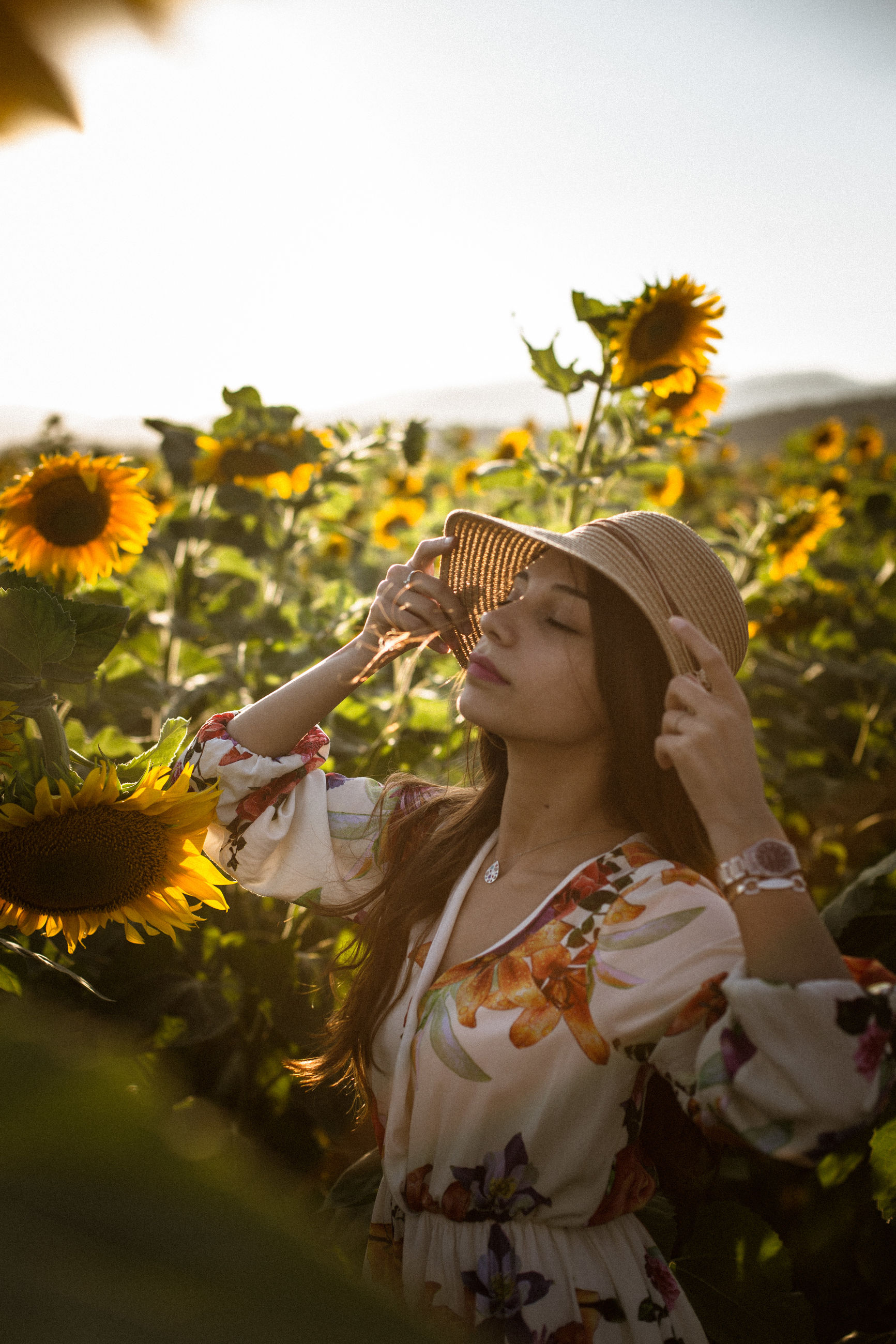 Young woman with eyes closed wearing hat standing amidst sunflowers
